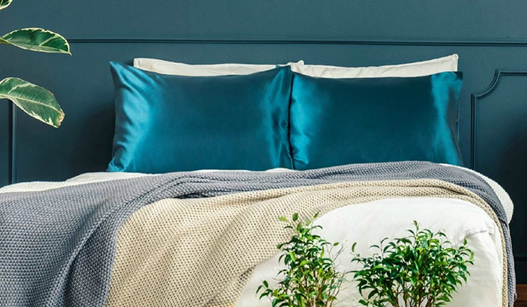 Teal satin pillow cases on bed