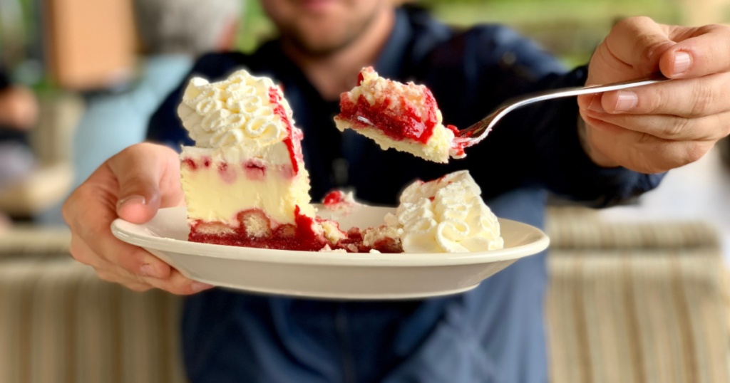 man holding plate with a slice of cheesecake from The Cheesecake Factory