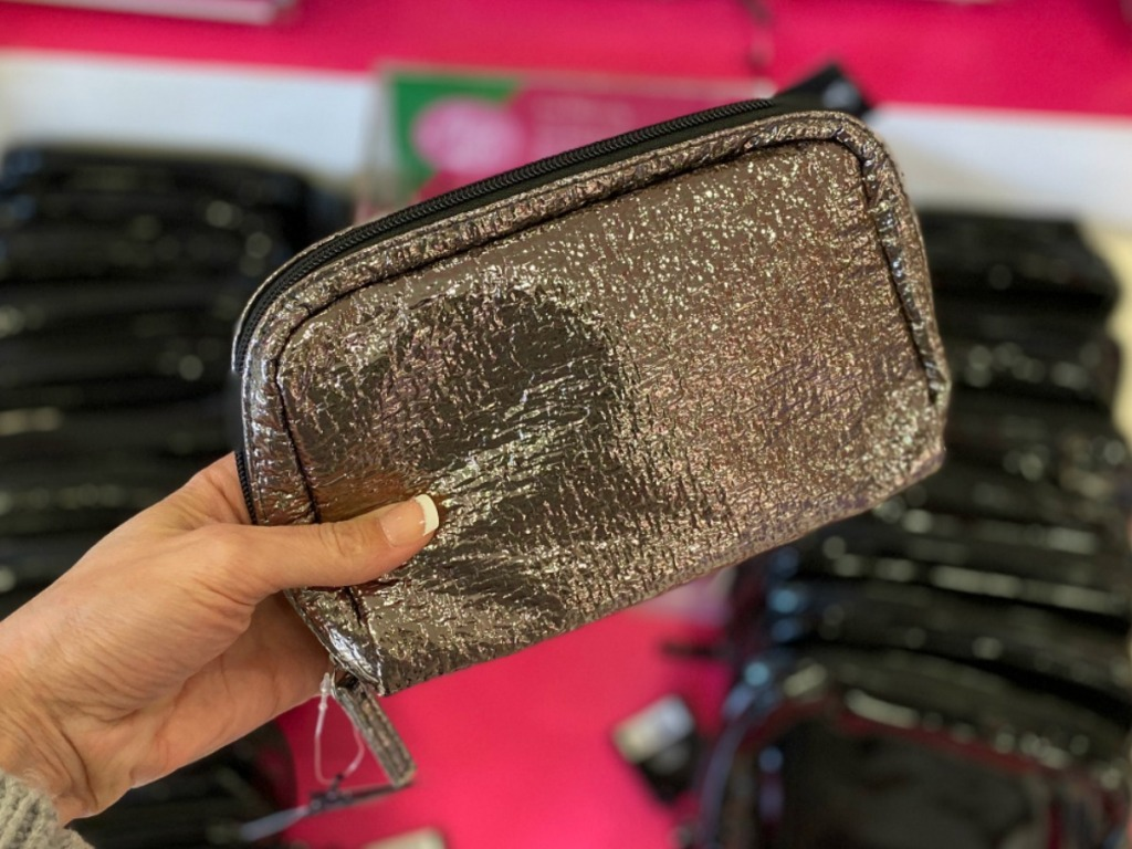 Woman holding a shiny Makeup bag filled with freebies