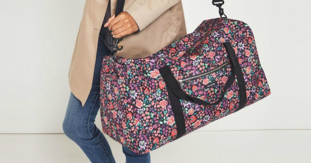 Woman carrying a floral printed duffel bag
