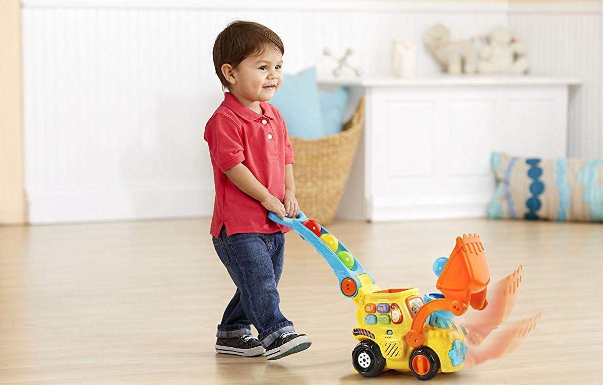 boy pushing a Vtech Bulldozer