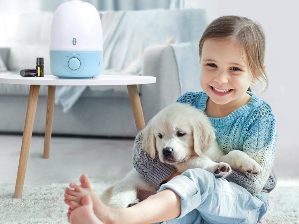 Baby whale humidifier on a side table next to a girl holding a dog