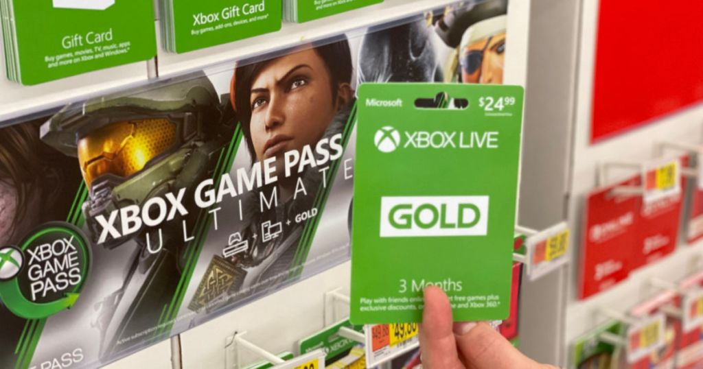 woman holding Xbox Live Gold card with xbox game pass ultimate banner in the background