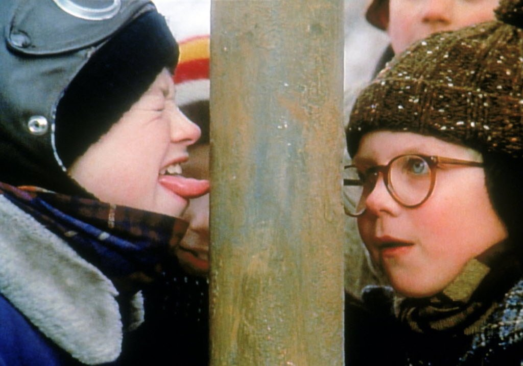 two boys standing next to pole with tongue sticking on it