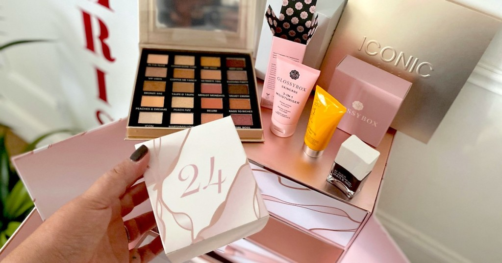 hand holding 24 box with various makeup beauty products behind it