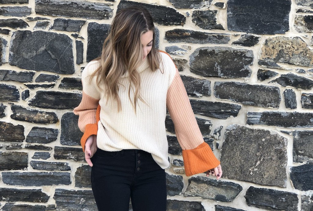 woman wearing a beige and orange sweater