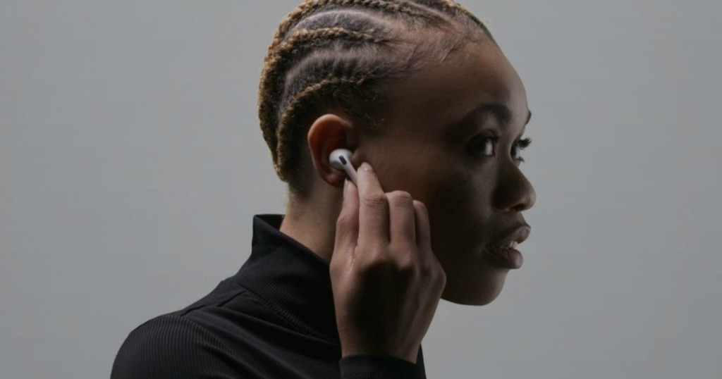 woman holding earbud in ear