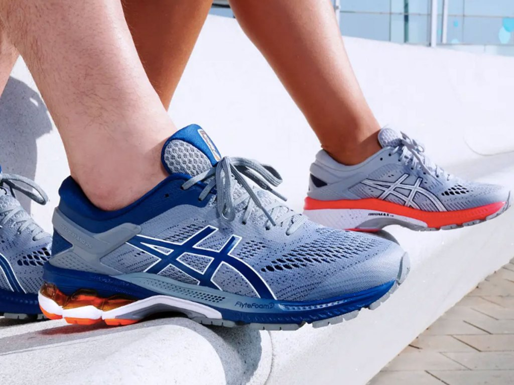 man and woman sitting on a track wearing Asics Kayano running shoes