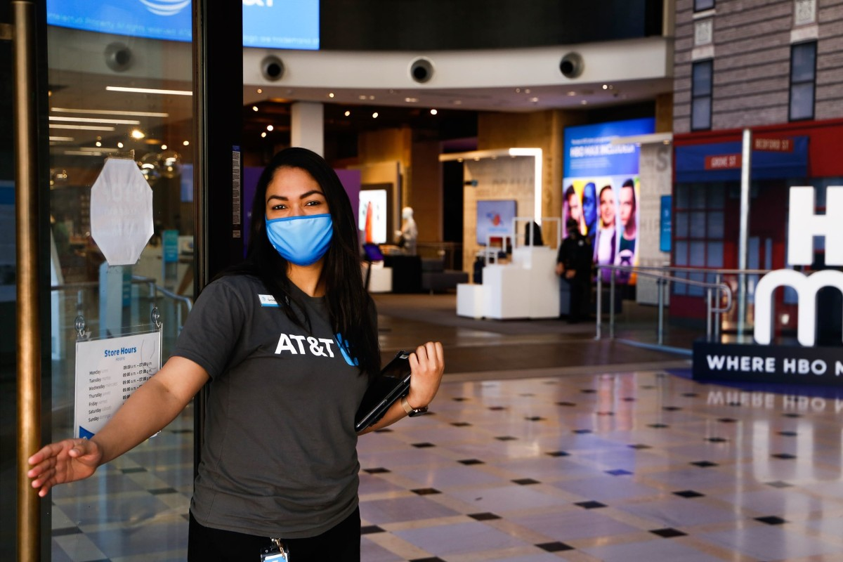 masked woman opening door at AT&T store