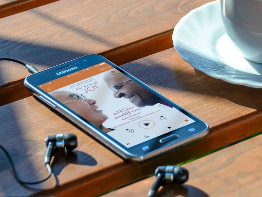 phone and headphones on table outdoors with coffee cup