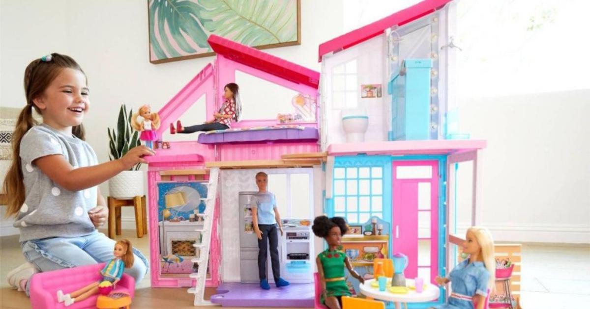 little girl playing with barbie malibu house