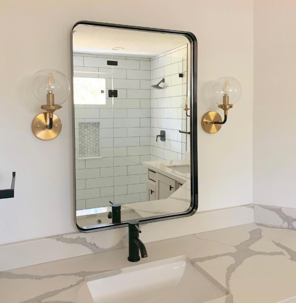 black rectangular mirror hanging in bathroom above sink and next to gold globe sconces