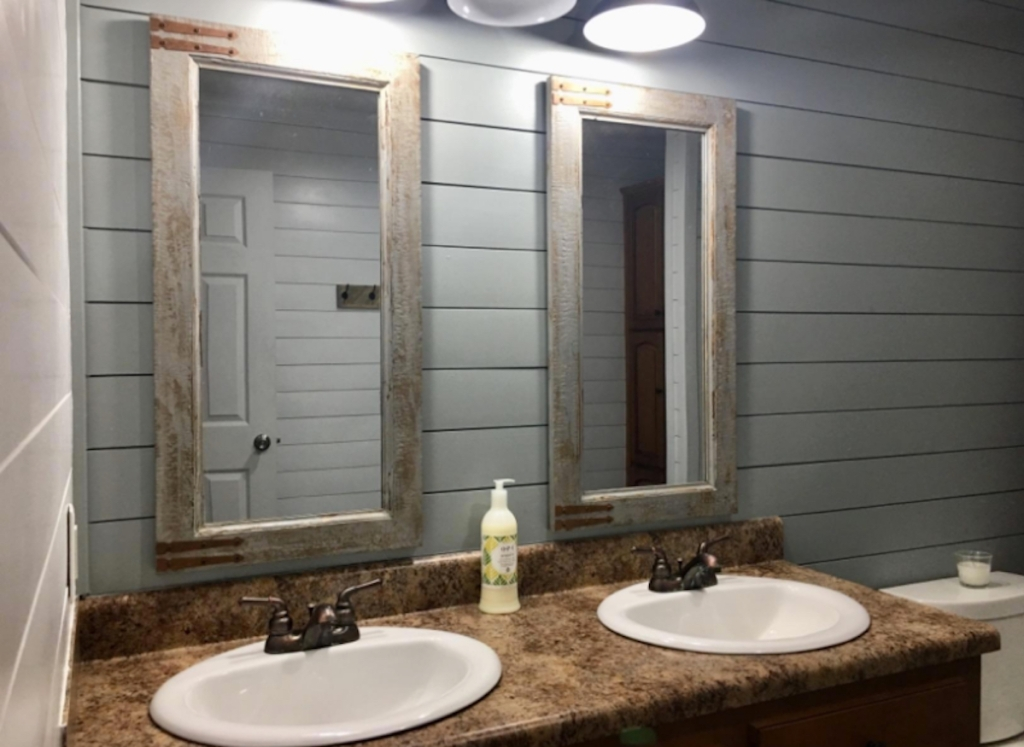 two rectangular mirrors hanging in bathroom with white vanity sinks