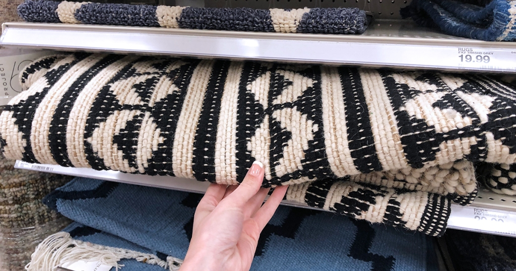 hand holding black and cream geometric rug on store shelf