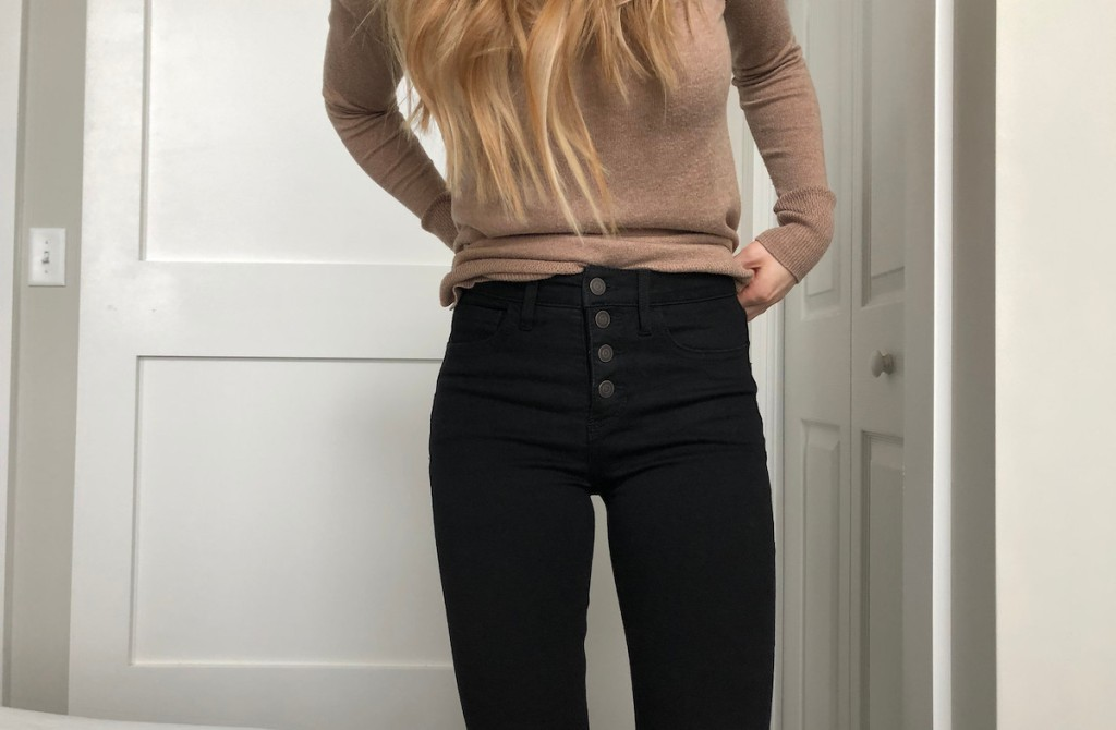 woman wearing black jeans and brown sweater
