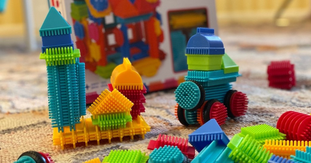 different shapes of colorful bristle blocks on floor with box