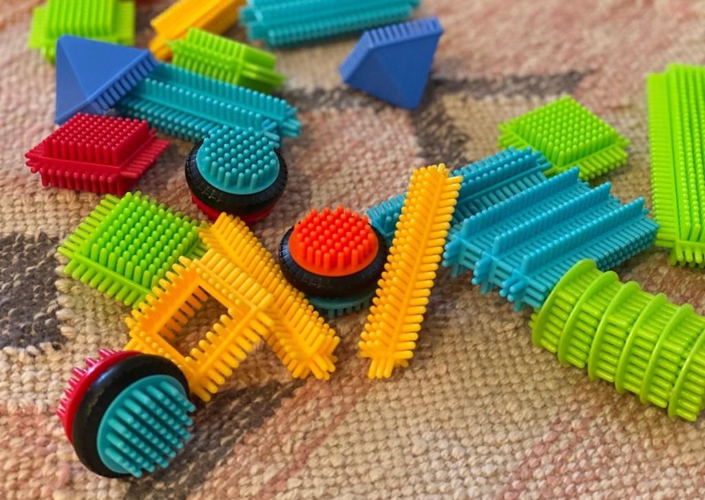 colorful random bristle blocks scattered on rug floor