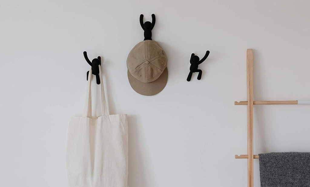 black decorative buddy wall hooks on wall with hat and bag