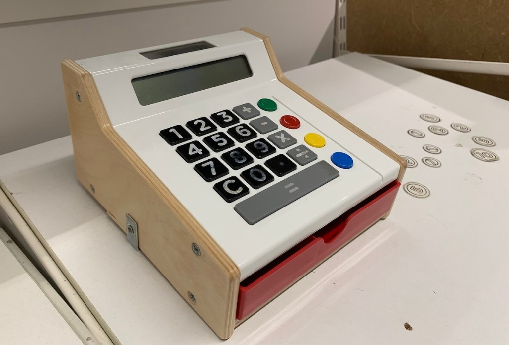 wooden toy cash register on white IKEA shelf with coins