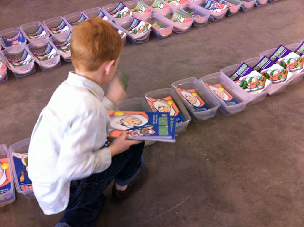 boy filling clear totes with christmas stuff