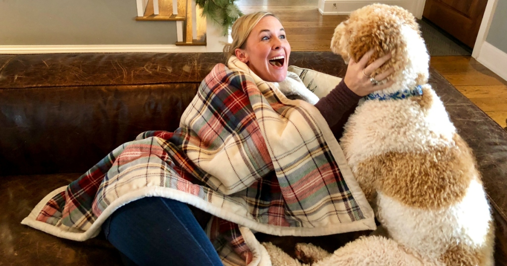 woman with cuddl duds sherpa throw wrapped around her with dog on couch