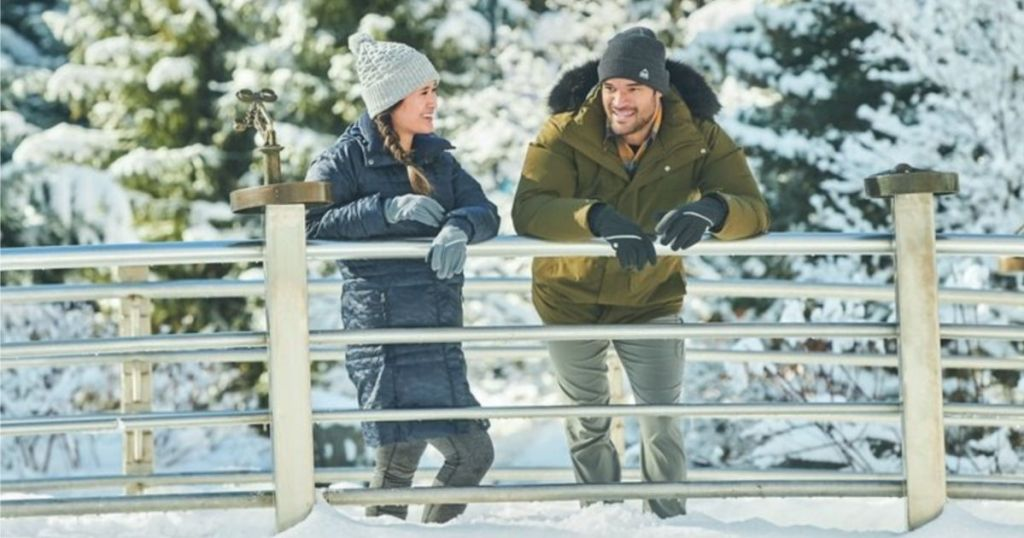man and woman wearing columbia winter jackets on a bridge in the snow