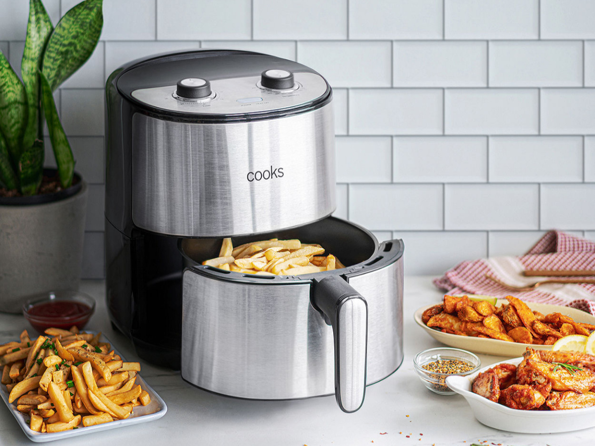 stainless steel cooks air fryer with basket out showing fries and fried foods in background