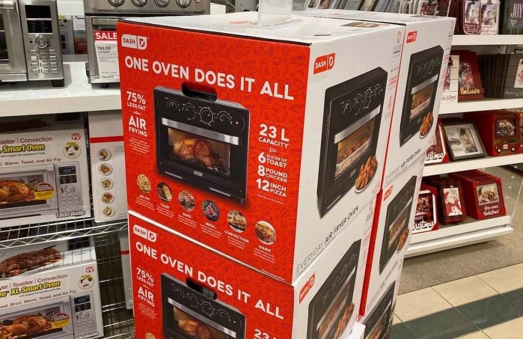 black dash air fryer ovens in red boxes stacked in store