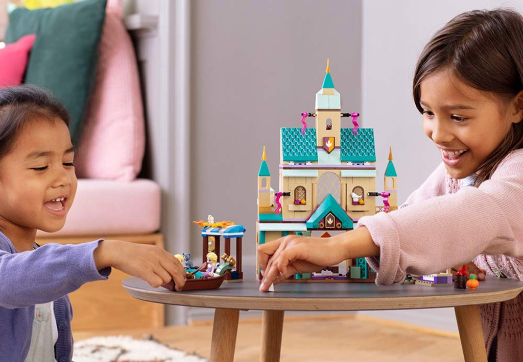 girls playing with disney frozen arendale castle lego set