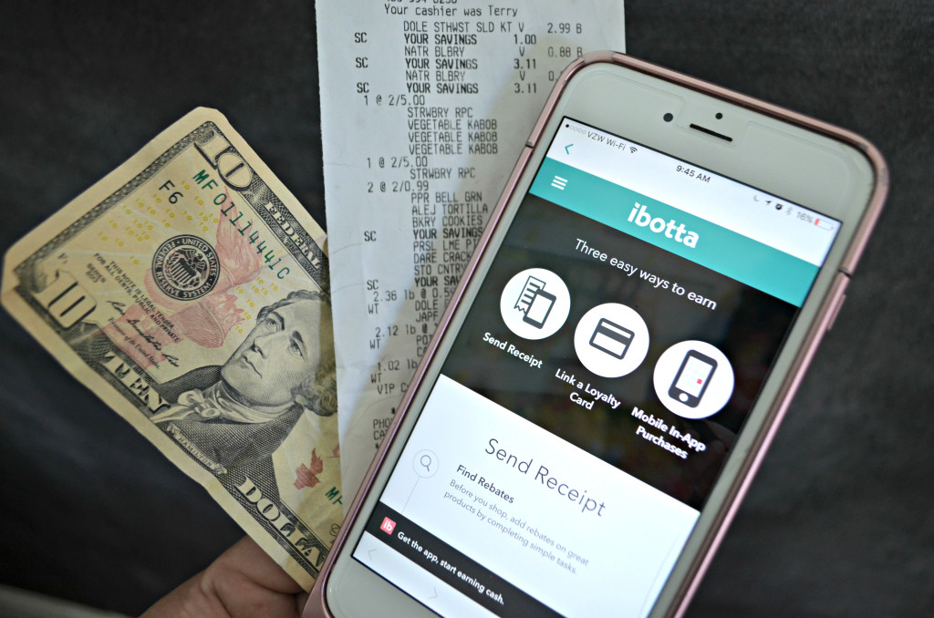 ibotta app on phone next to receipt and $10 bill