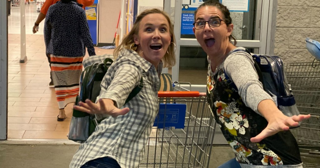two woman pushing Walmart cart who are excited to shop