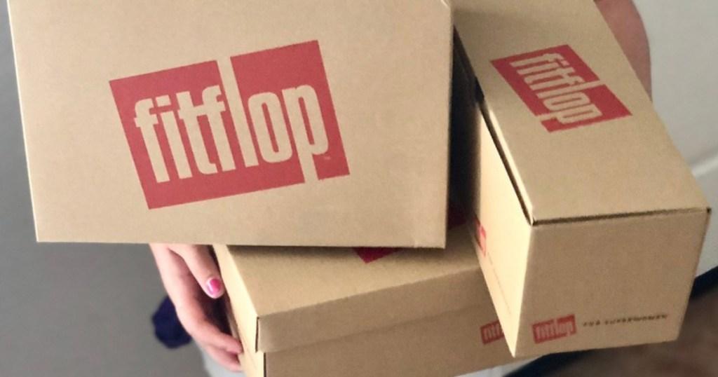 person holding fit flop shoe boxes