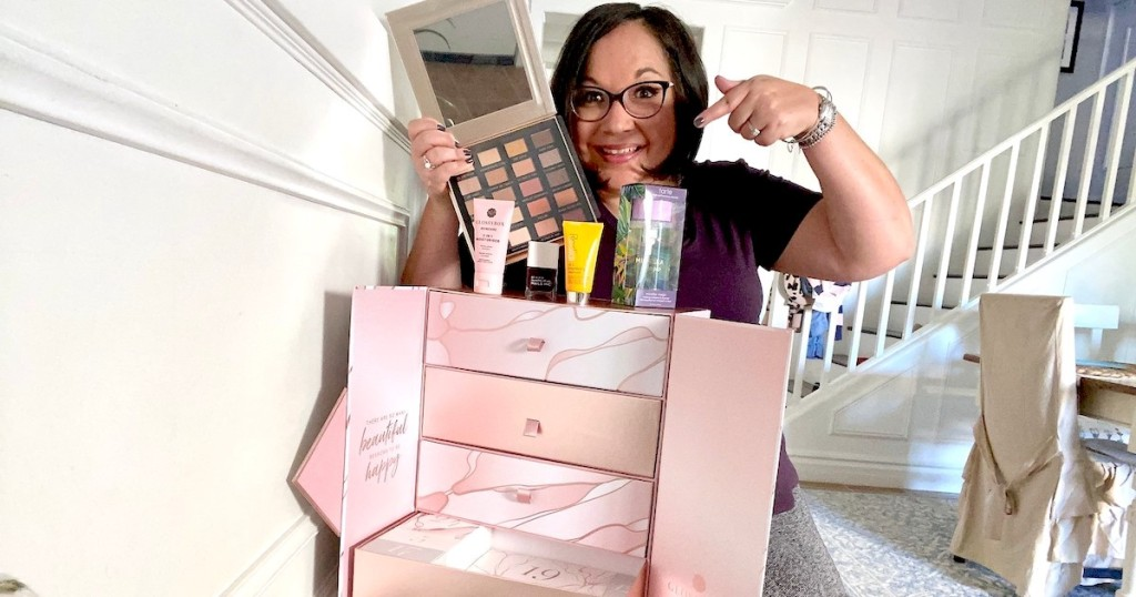 woman holding up eye shadow pallet with glossy beauty advent calendar box