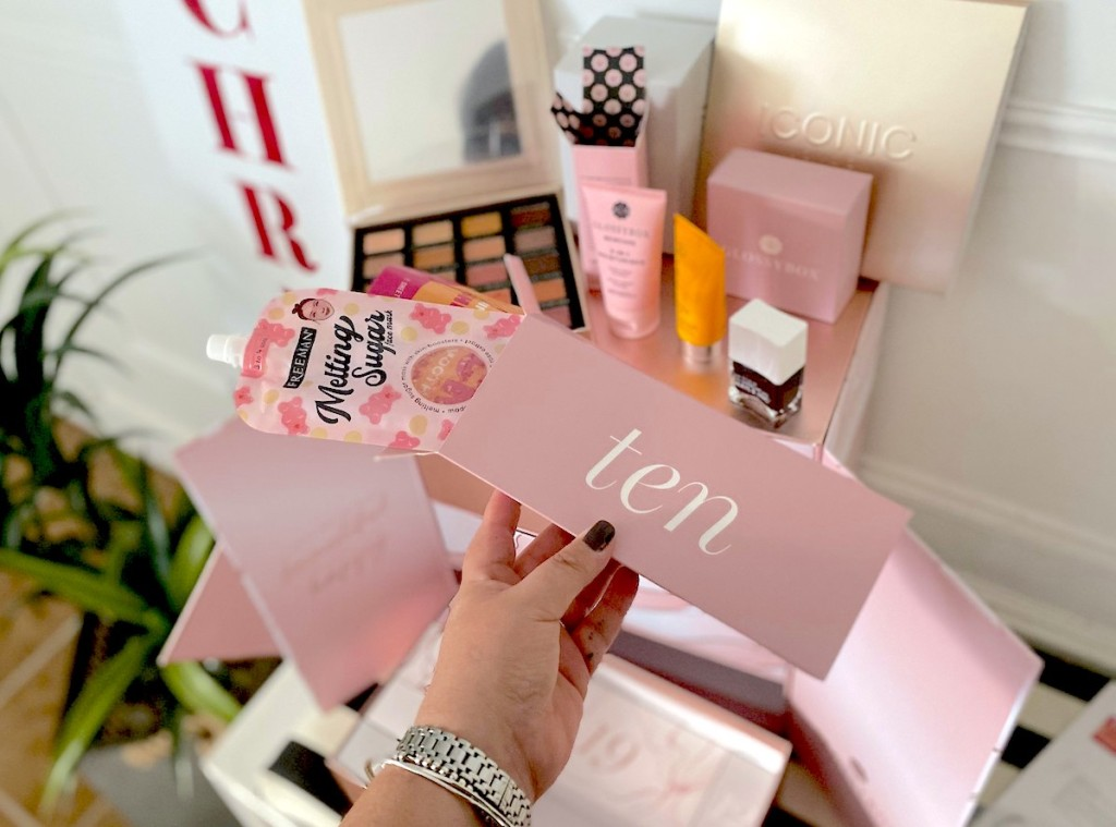 hand holding ten box with beauty makeup behind it