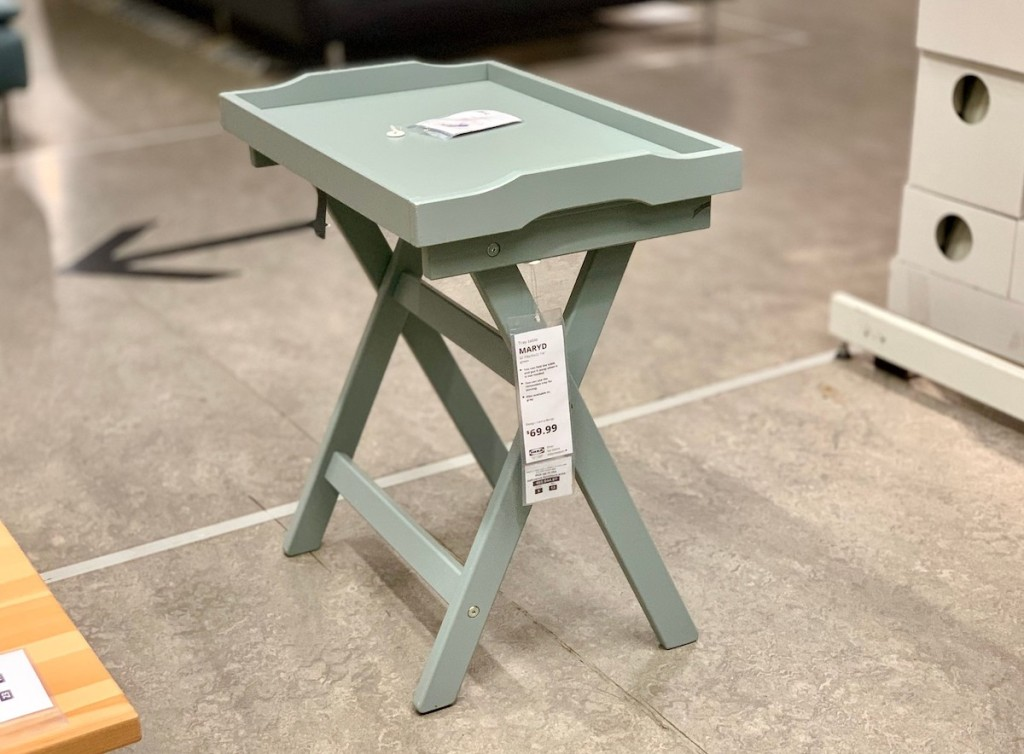 ikea sage green tray table sitting in middle of concrete floor
