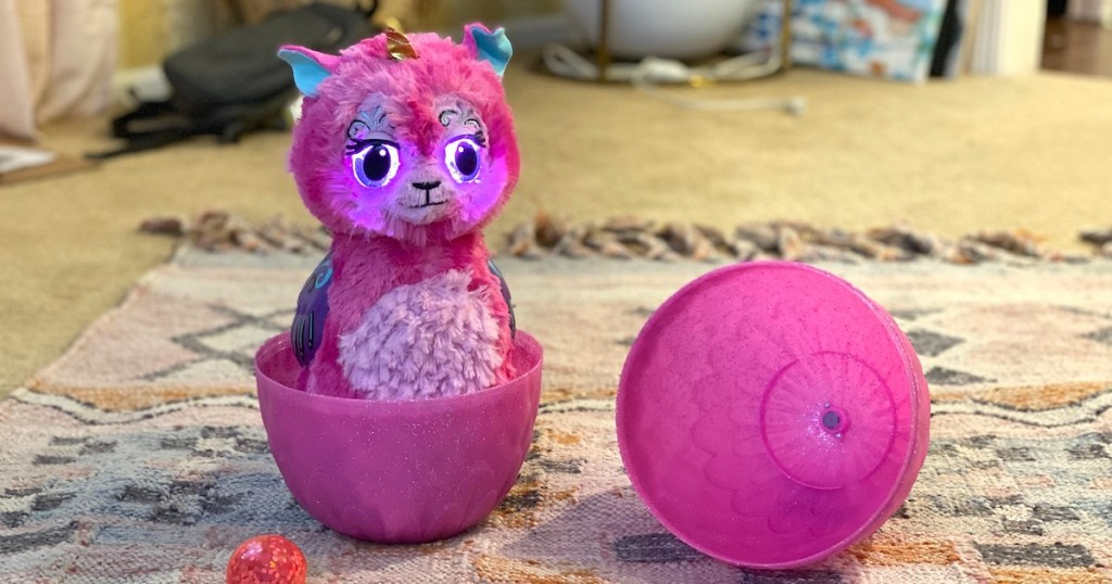 pink hatchimal toy that grows sitting on rug