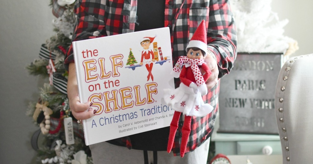 holding an elf on the shelf by the tree