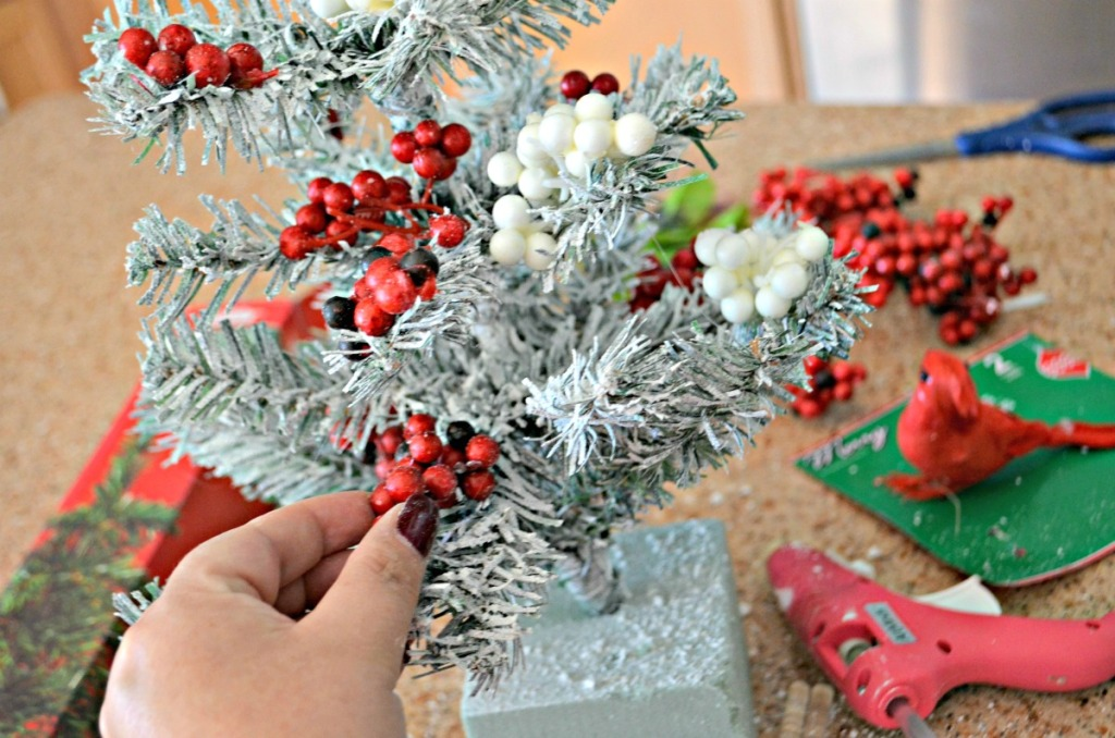 hot gluing berries to dollar tree christmas tree