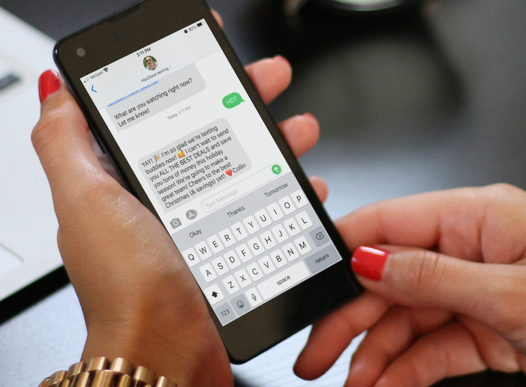 woman holding cell phone with hot texts on screen