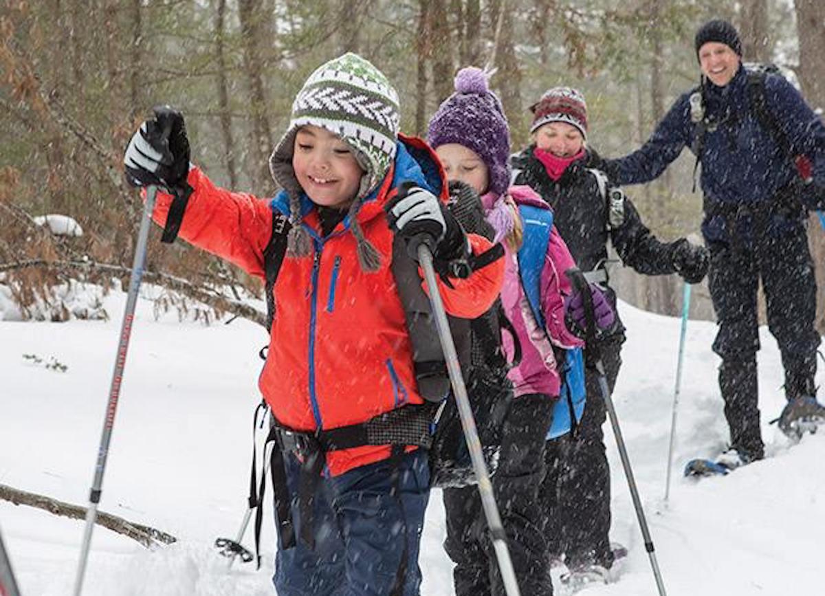 kids walking through snow with skis