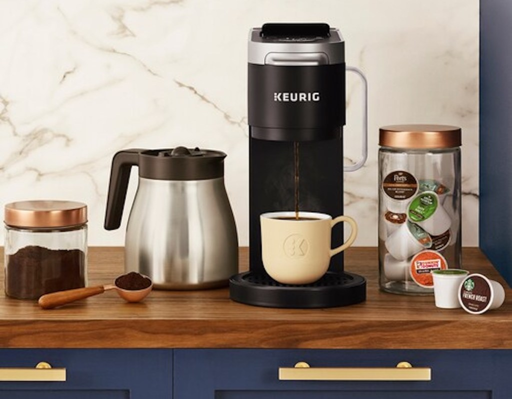 black and silver keurig with coffee pot and k cups