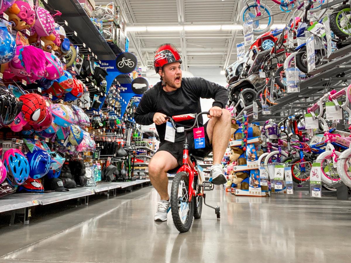 man riding on child's training bike