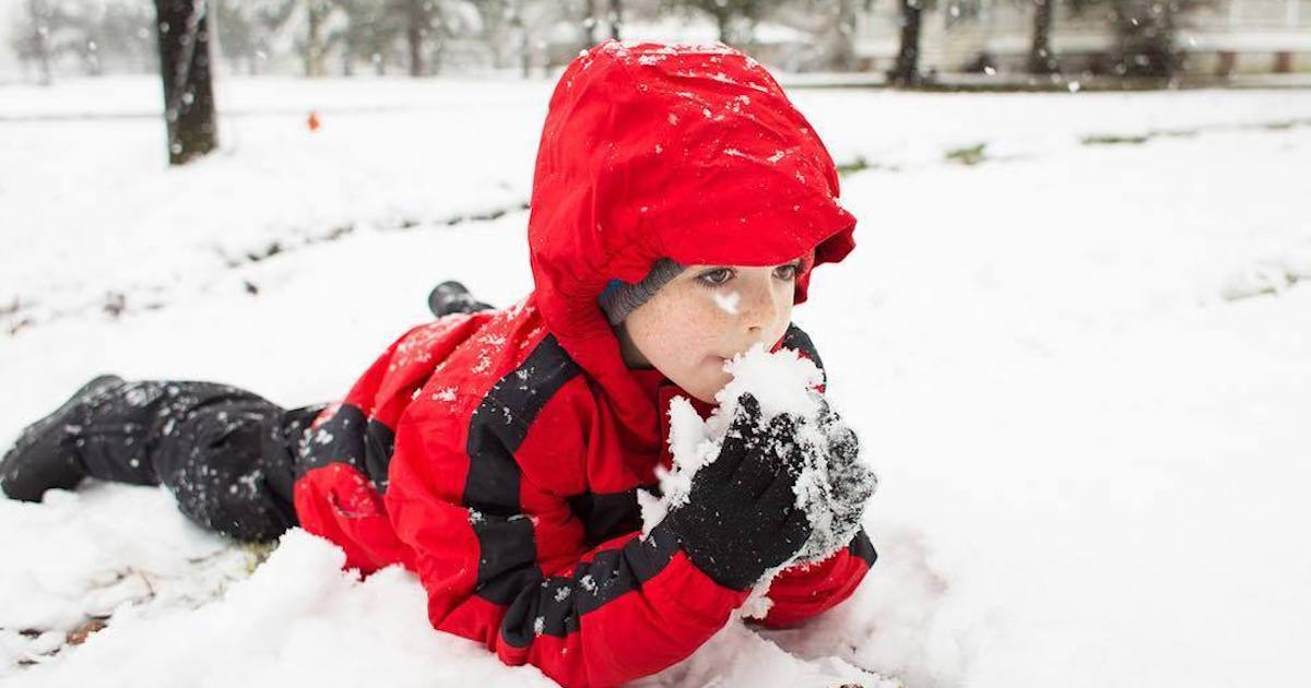 kid laying in snow wearing red jacket