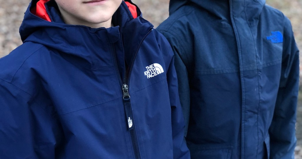 two kids wearing blue north face jackets outside