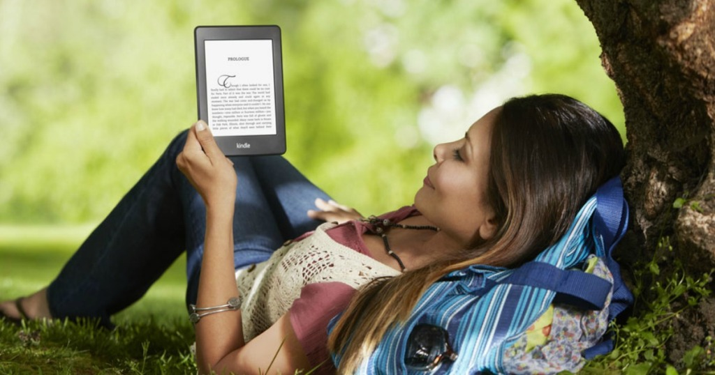 woman laying outside reading on a tablet