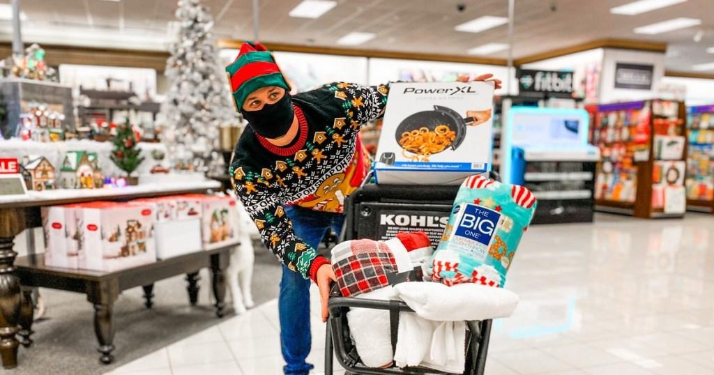 pria bertopeng dan topi Natal mendorong gerobak di Kohl's