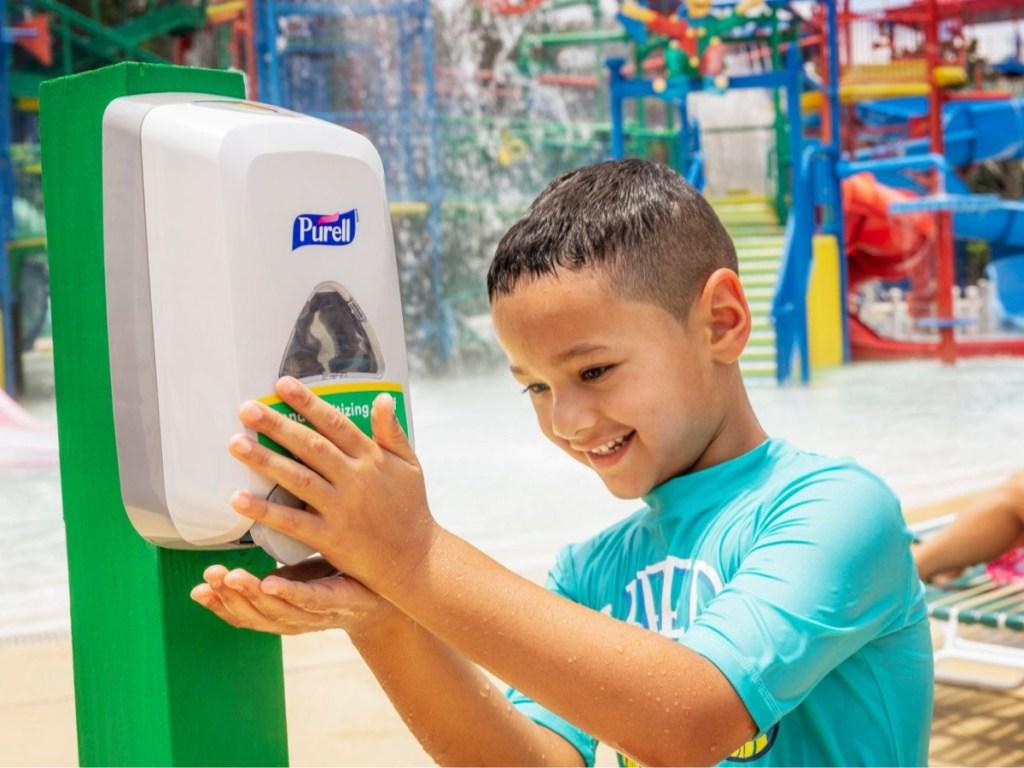 boy at water park using hand sanitizer