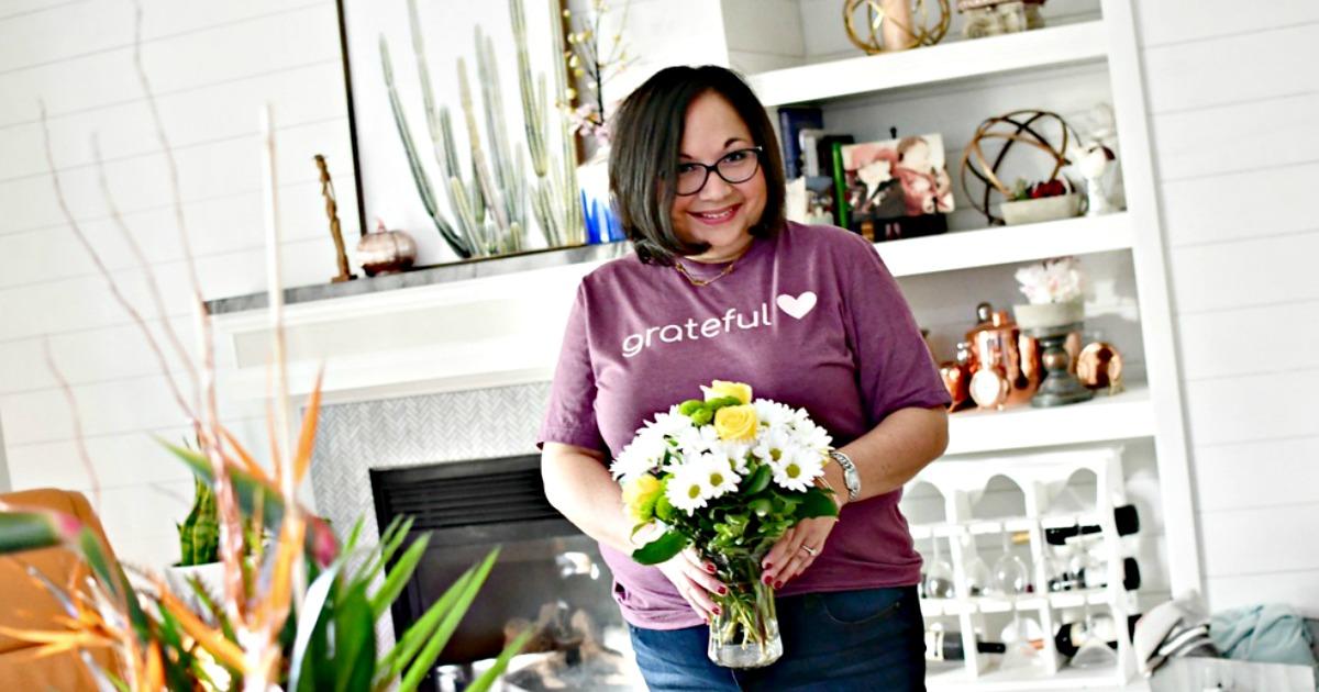 Lina wearing purple grateful tee holding flowers