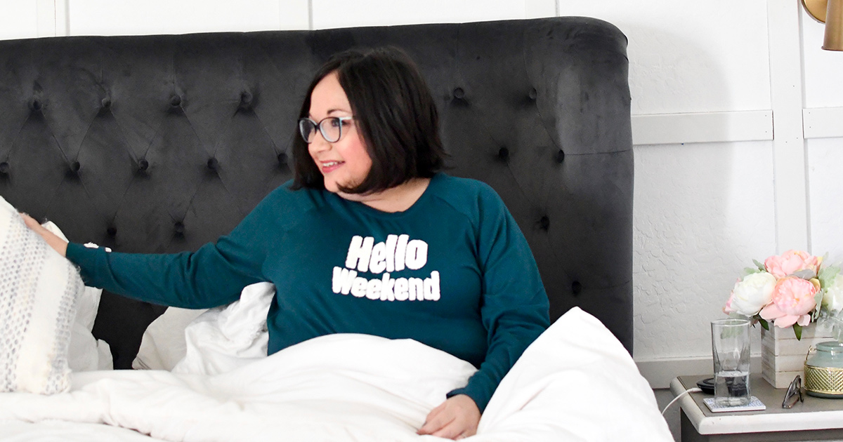 """Lina wearing Walmart pajamas in bed with her shirt reading """"Hello Weekend"""""""