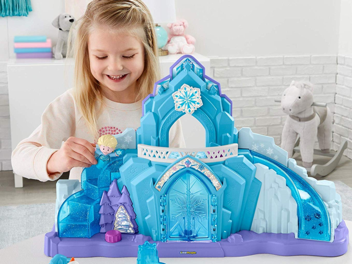 little girl playing with frozen ice castle and figures